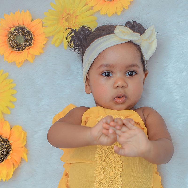 Bébé allongé avec les fleurs jaunes qui fait des signes pour bébé