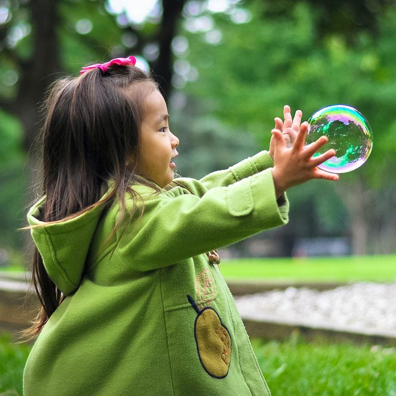 Petite fille qui joue avec une bulle
